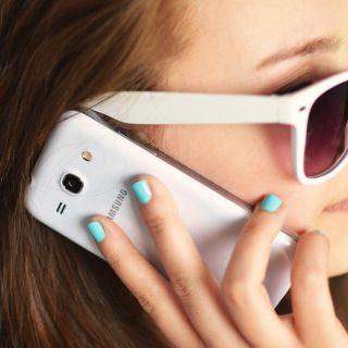 Dziewczyna rozmawiająca przez telefon w okularach przeciwsłonecznych.