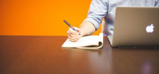 mężczyzna piszący na biurku
